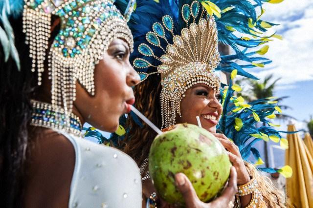 Samba dancers in costume, drinking coconut drinks, Ipanema Beach, Rio De Janeiro, Brazil