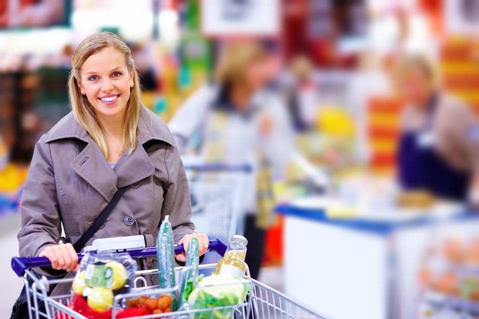 Happy Modern pushing trolley in supermarket