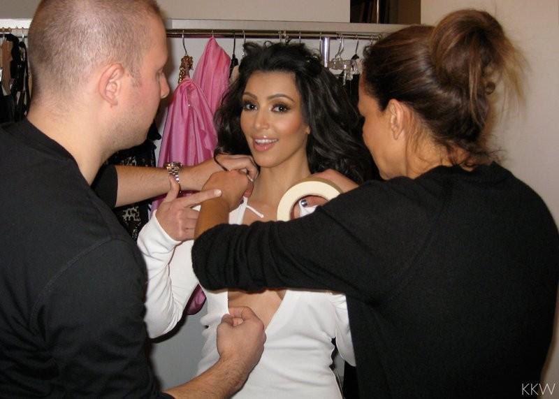 Equipe da socialite ajudando a colar as fitas no corpo de Kim
