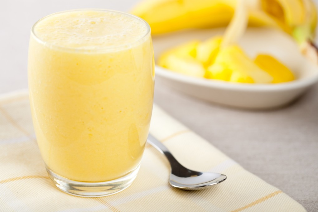 Banana pineapple smoothie freshly made with banana in background