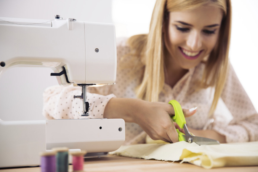 Smiling female designer cutting cloth