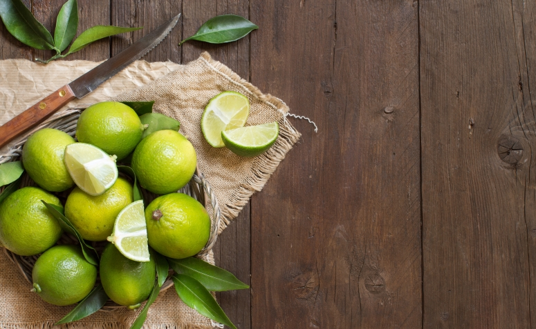Fresh limes with knife and leaves on a wooden  table