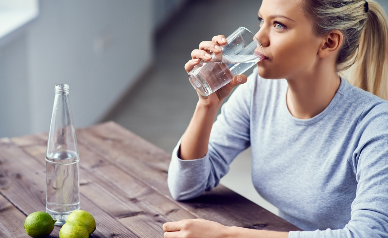 Young woman drinking water with lime in the morning