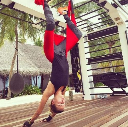 A modelo Natasha Poly usando o Yoga Aéreo para fazer alongamento